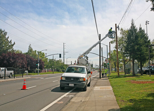 Utility workers move lines to new poles